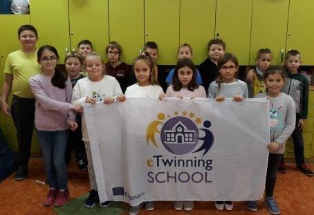 Grupa dzieci z klasy 3a trzyma flagę z napisem Szkoła eTwinning