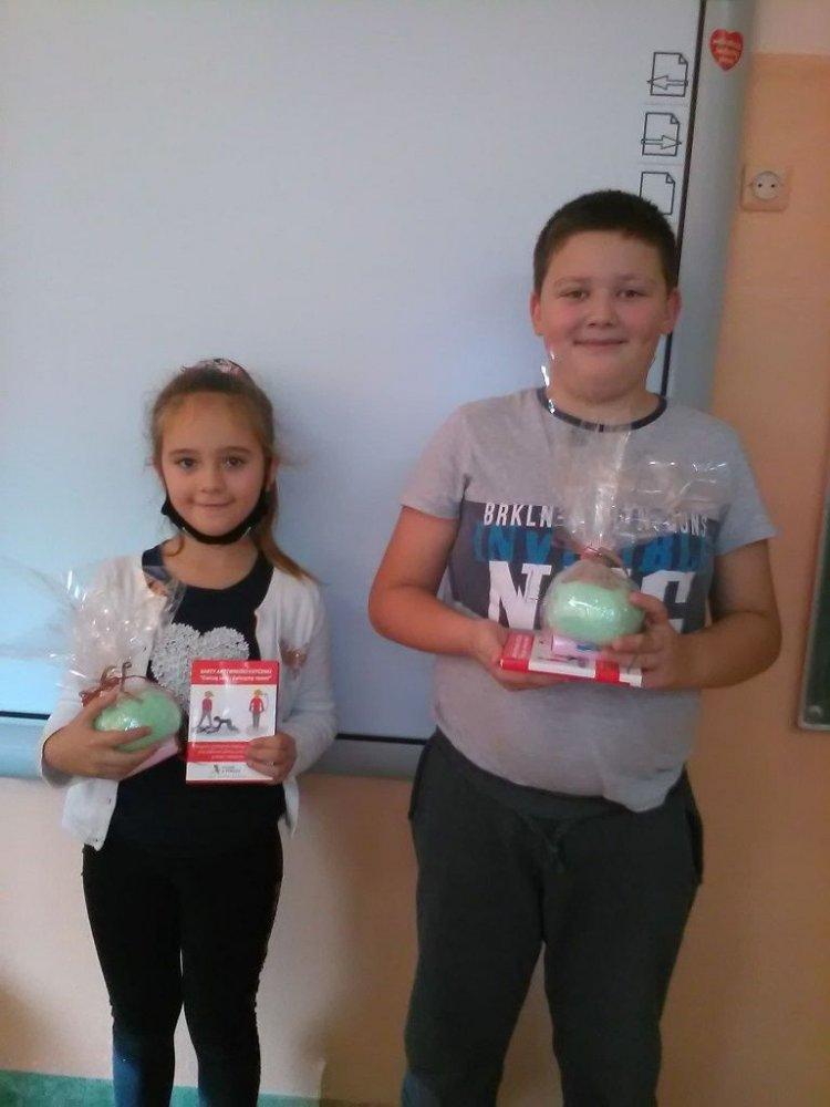 Dwoje dzieci chłopiec i dziewczynka stoją na tle tablicy szkolnej i trzymają wygrane nagrody.