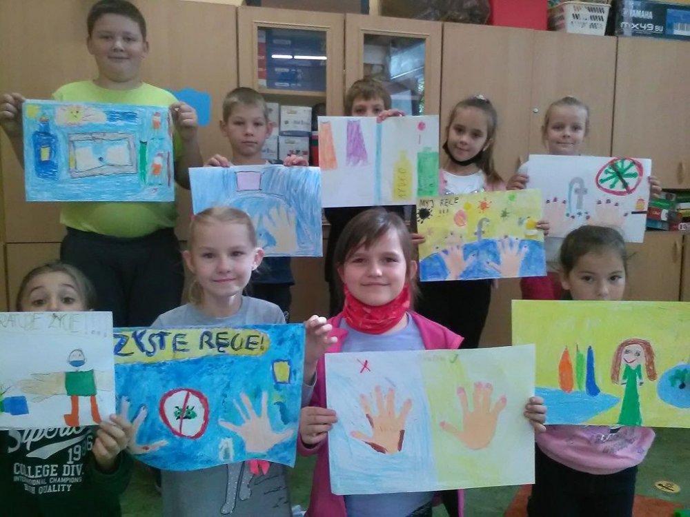 Grupa dzieci stoi i trzyma w rekach przygotowane przez siebie kolorowe prace konkursowe.