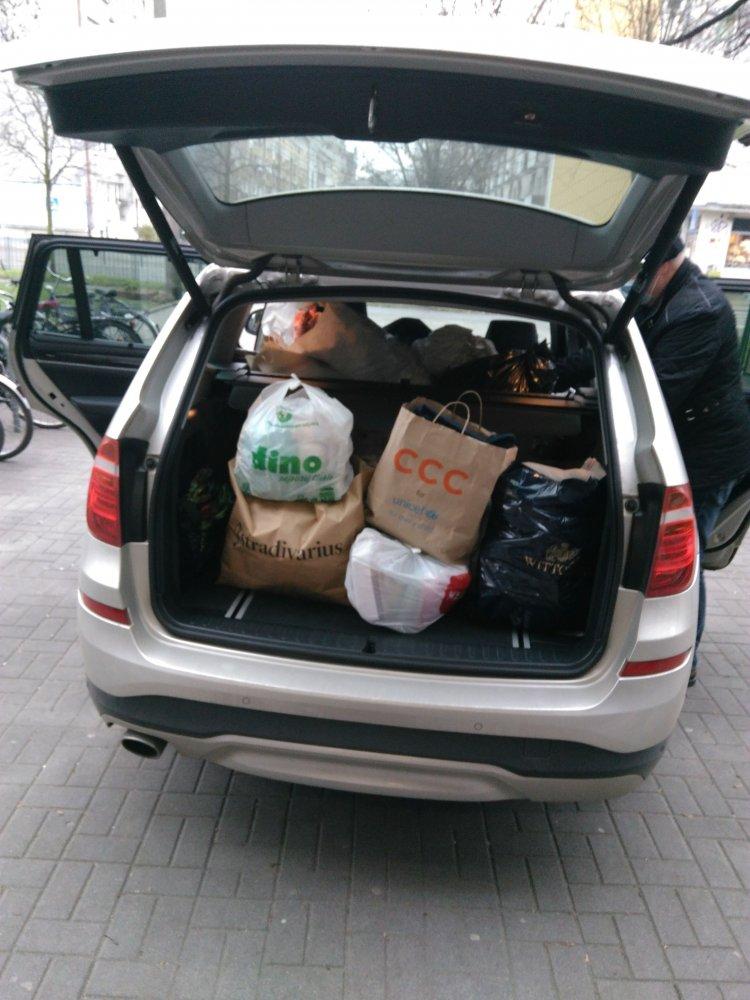 Otwarty bagażnik samochodowy wypełniony torbami z darami dla Polaków na Kresach.