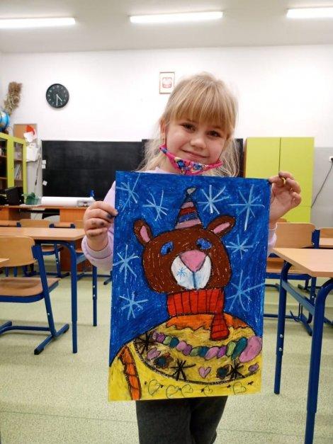 Dziewczynka stoi w klasie i trzyma w rękach pracę formatu A3 przedstawiającą brązowego misia na niebieskim tle.