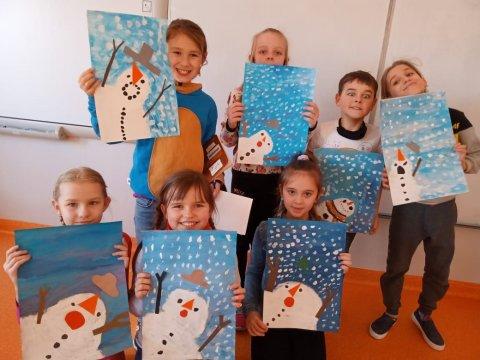 Grupa uczniów trzyma w rękach prace wielkości A3 przedstawiającą zimowe bałwanki na niebieskim tle.
