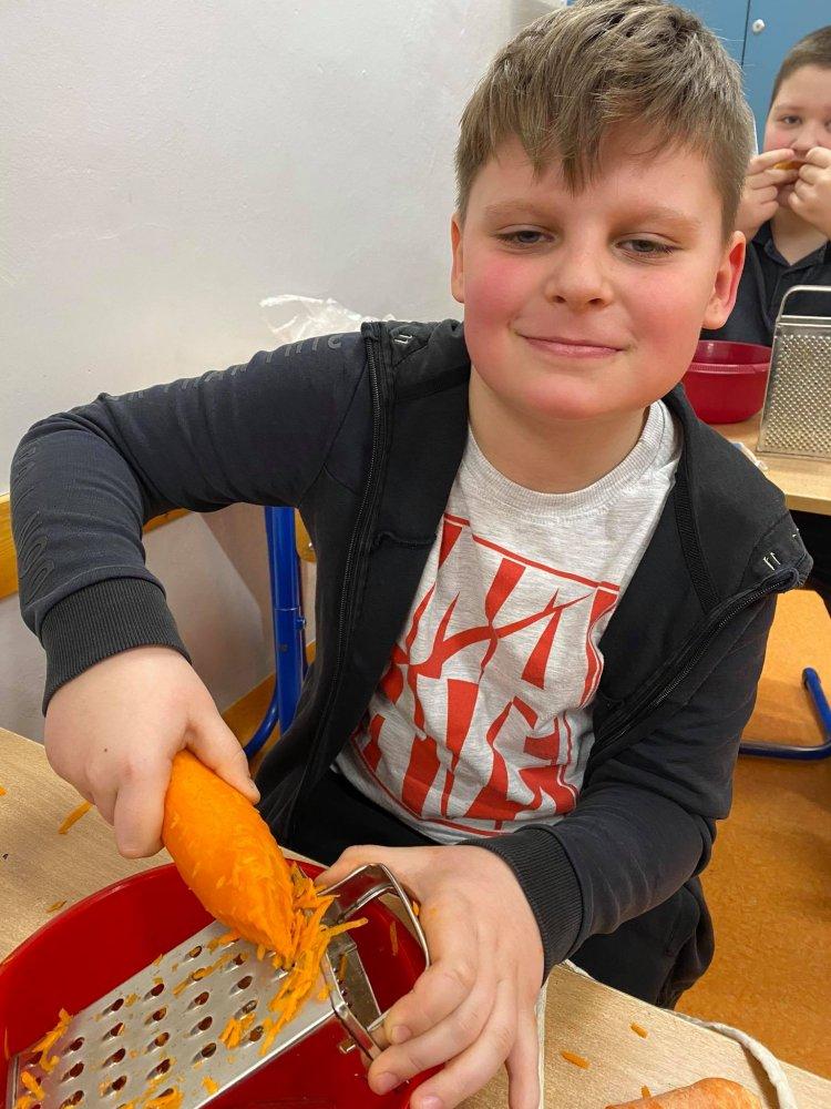 Chłopiec przygotowuje surówkę z marchewki i jabłek.