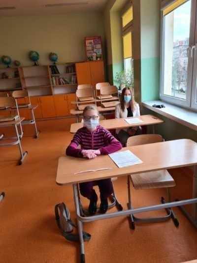 Uczennica  w klasie siedzi przy ławce. Na twarzy ma założoną maseczkę.