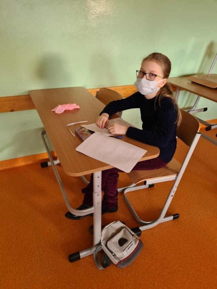 Uczennica w klasie siedzi  siedzi w ławce. Na twarzy ma okulary oraz założoną maseczkę ochronną.