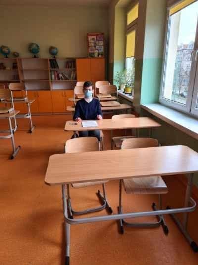 W klasie widoczne są ławki. Przy jednej z nich siedzi uczeń. Na twarzy ma założoną maseczkę.