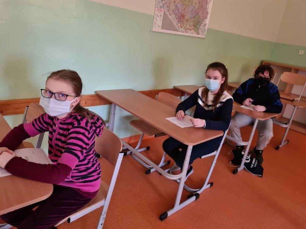 Troje uczniów w klasie siedzących przy ławkach szkolnych. Każdy z nich ma na twarzy założoną maseczkę ochronną.