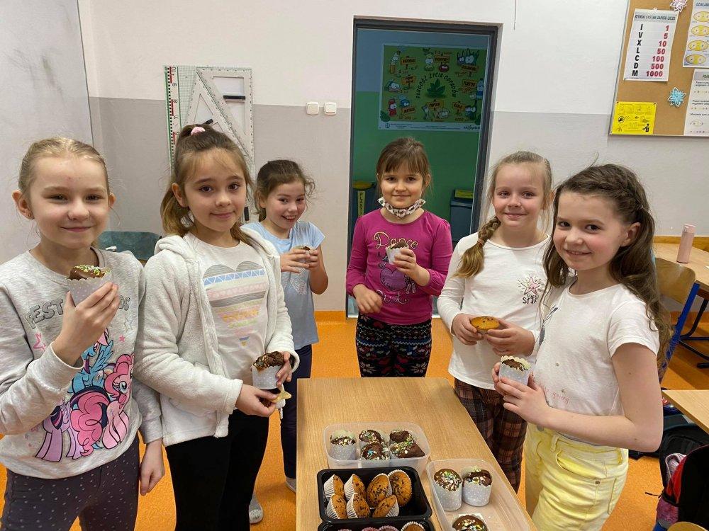 Dziewczynki jedzą babeczki.
