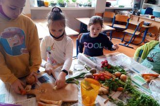 Troje uczniów w klasie sadzi rośliny do doniczki