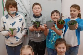 Kilku uczniów pokazuje doniczki z posadzonymi przez siebie roślinkami