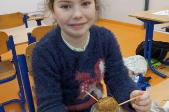 dziewczynka w klasie prezentuje posadzoną roślinkę